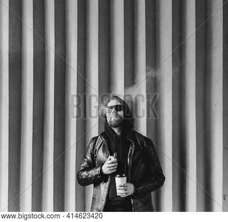 Vape Man. Portrait Of A Handsome Young Bearded Guy In Vaping An Electronic Cigarette Opposite The Fu