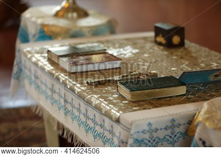 Ecclesiastical Books And Cross On Communion Table In Church. Baptism Ceremony