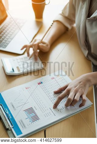Business Woman Using A Calculator To Calculate Working On Desk In Home Office. Consultant, Financial