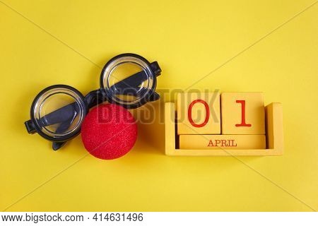 April Fools Day Background. Numbers Cube With Clown Glasses And Nose On Yellow Background