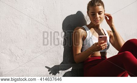Fitness Woman Jogger Sit On Floor With Phone And Earphones. Sportswoman Resting After Jogging, Train