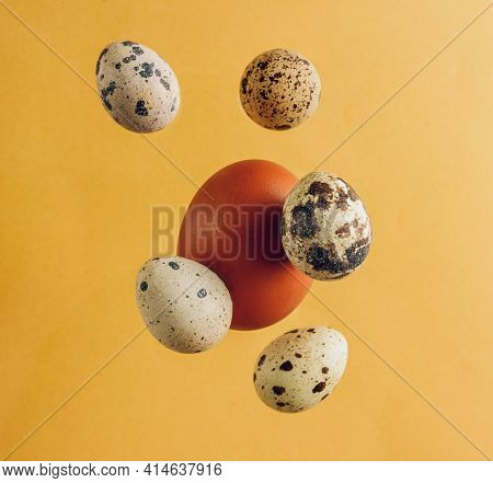 Falling Chicken And Quail Eggs, Isolated On Yellow Background, . Easter Concept.