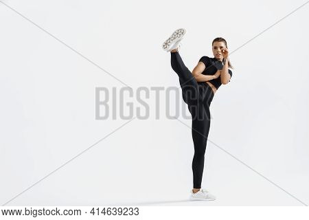 Girl Practicing Tae-bo Exercises, Kicking Forward With Legs. Photo Of Sporty Girl Isolated On White