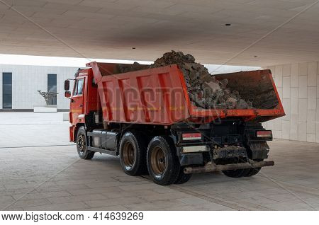 Dump Truck With A Red Cab And Body Is Driving In A Tunnel. The Body Is Loaded With Earth And Stones.