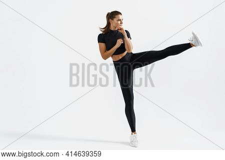 Motivation And Sport. Determined Sportswoman Athletic Fit Body, High Kick, Raising Legs, Punching Ai
