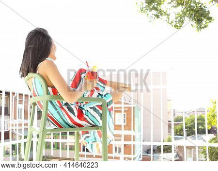 Low Angle Side View Of Unrecognizable Female Resting On Chair On Balcony While Enjoying Fresh Aperol