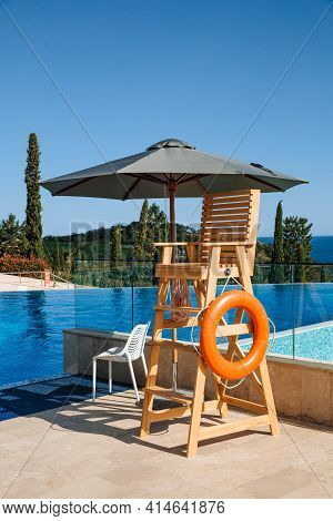 The Lifeguard's Post Is Under A Sun Umbrella. A Life Preserver Hangs Nearby. Water Safety Concept.
