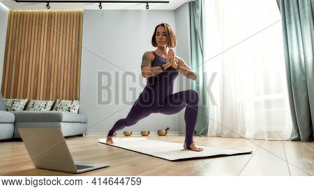 Girl Standing In A Rack And Conducting A Yoga Workout. Sports Girl Coach Conducting Online Lesson At