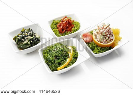 Composition Of Oriental Appetizers In Bowls, Isolated On A White Background. A Pickled Seagrass Japa