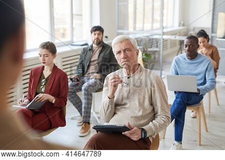 Diverse Group Of Business People Sitting On Chairs In Audience During Meeting Or Seminar, Focus On I