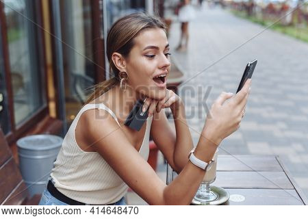 Wow Young Girl Is Surprised, Looking Into The Phone Screen And Holding A Credit Card. The Shocked Wo