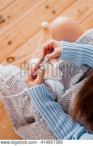 A Girl In A Blue Sweater Knits With Knitting Needles. Womens Hands Knit With Knitting