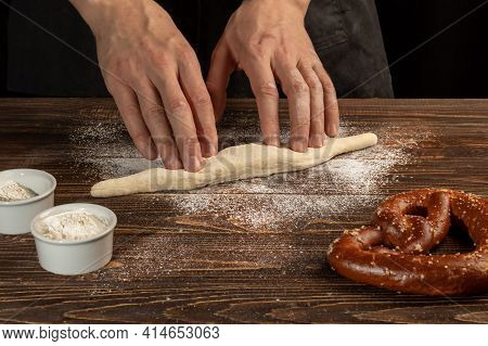 Step-by-step Instructions For Making Pretzels. The Cook Rolls Out The Dough And Rolls Out The Pretze