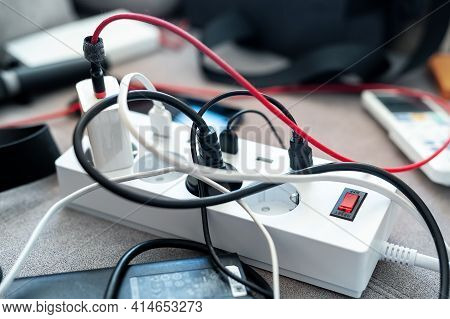 Overloaded Power Socket Plug Extendion At Home. Tangled Cords Of Home Appliances And Chargins Gadget