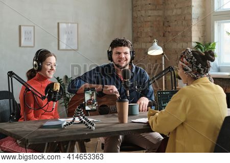 Radio Dj Interviewing Musical Couple During Broadcasting On The Radio