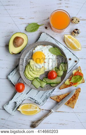 Vertical Composition Of A Plate With Scrambled Eggs, Toast With Avocado And Tomatoes, Juice And Lemo