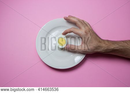 A Boiled Egg Cut In Half On A Plate. The Hand Reaches For Food. Healthy Breakfast. Boiled Egg On A P