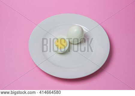 A Boiled Egg Cut In Half On A Plate. Healthy Breakfast. Boiled Egg On Pink Background