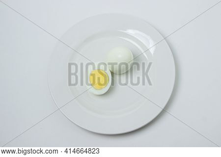 A Boiled Egg Cut In Half On A Plate. Healthy Breakfast. Boiled Egg On White Background