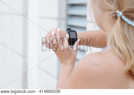Close-up Image Of Female Jogger Checking Fitness Trekker After Training Outdoors