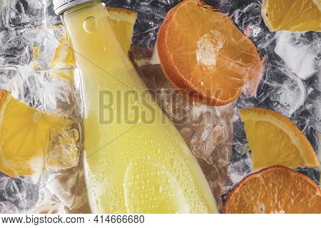 A Bottle Of Summer Fresh Cold Soda Lemonade In Water With Ice Cubes And Slices Of Oranges And Fruit.