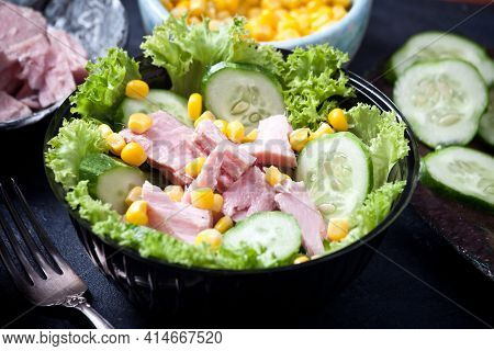 Fresh Tuna Salad With Corn And Lettuce Leaves, Sauce And Fresh Cucumbers, On A Black Plate On Dark S