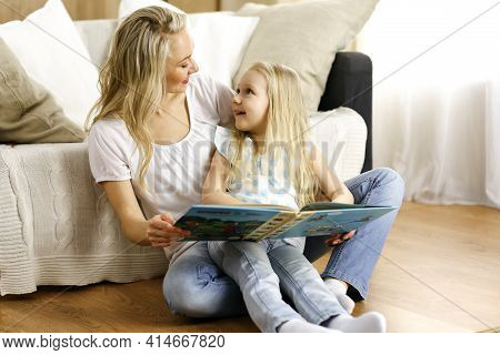 Happy Family. Blonde Young Mother Reading A Book To Her Cute Daughter While Sitting At Wooden Floor.