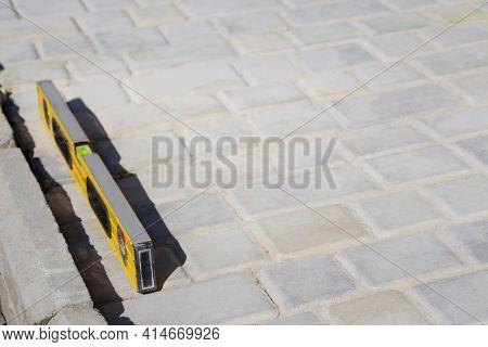 Defocus Paving Backyard Patio Background Of Stone Floor Texture. Yellow Spirit Level On Paving Stone