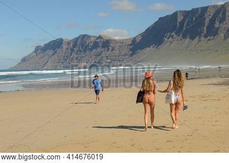 People Walking On Famara Beach At Lanzarote In Canary Islands, Spain