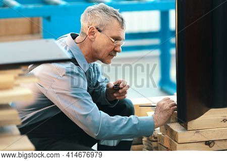 An Elderly Worker Carefully Restores Furniture In A Carpenter's Workshop During The Day. A Mustachio