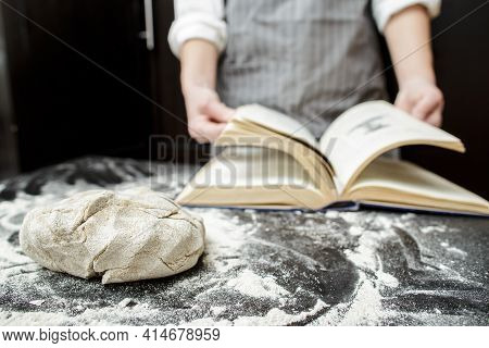 Kneaded Dough Lies On A Table Sprinkled With Flour, Against The Background Of A Baker Leafing Throug