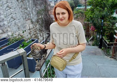 Young European Woman Caresses Turkish Stray Cat In Antalya.