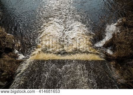 The Water Of The Fast Wild River Falls From The Concrete Locks Forming A Waterfall And Flows Into Th