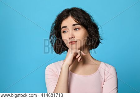 Woman Looking Sideways With Doubtful And Skeptical Expression.
