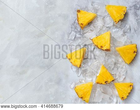 Pieces Of Ripe Pineapple, On Ice On A Gray Background.