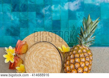 Summer Concept. Hat, Glasses, Pineapple, Flowers By The Pool.