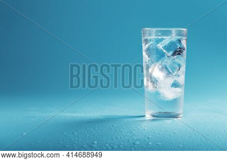 A Glass With Ice Water And Ice Cubes On A Blue Background.