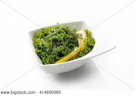A Pickled Seagrass, Seaweed Japanese Salad With Sesame, On A Green Decorative Lettuce, Isolated On W