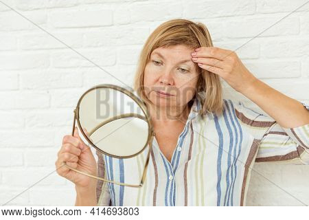 Sad Old Senior Mature Woman Looking At Face Reflection In Round Mirror, Unhappy With Wrinkled Skin,
