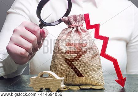 Woman Female Manager Examines A Indian Rupee Money Bag With A Red Down Arrow And Automobile. Electri