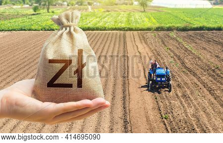 Hand With A Polish Zloty Money Bag On The Background Of A Farm Field With A Tractor. Land Lease, Lan