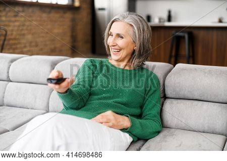 Cheerful Senior Woman Enjoys Evening With A Tv Shows, Series. Smiling Mature Woman Sits On The Sofa