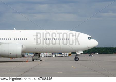 Nose And Fuselage With Airplane Windows On The Background Of The Airport Terminal