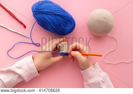 Childrens Hands In The Process Of Crocheting Toys From Blue And Beige Yarn.