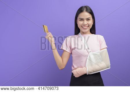 Portrait Of Young Woman With An Injured Arm In A Sling Holding A Credit Card Or Medical Insurance Ca
