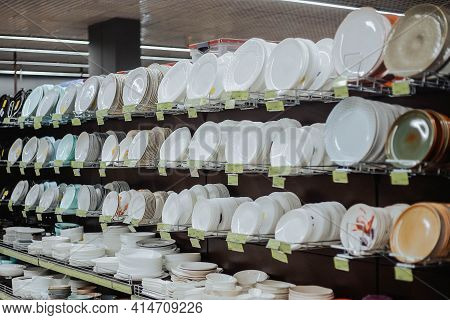 White Ceramic Plates On A Shelf In A Store. Assortment Of Dishes On Supermarket Shelves