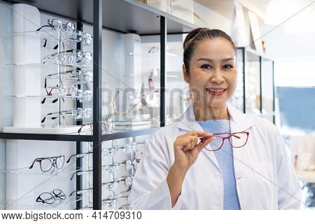 Asian Women Doctor Optometrist Smiling While Using Tablet And Recommend Customer To Choose Glasses B