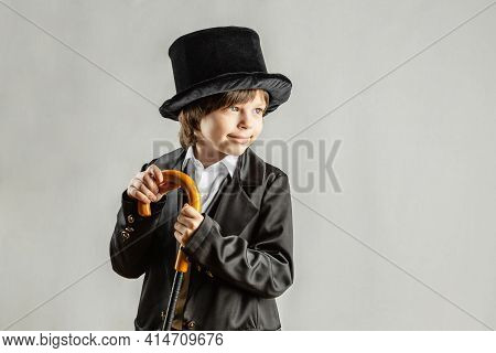 Young Six Year Old Boy Wearing Black Suit. Cosplay, Retro Party Or Halloween Costume Rental Concept