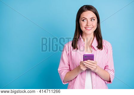 Photo Portrait Of Happy Woman Looking At Blank Space Holding Phone In Two Hands Isolated On Pastel B