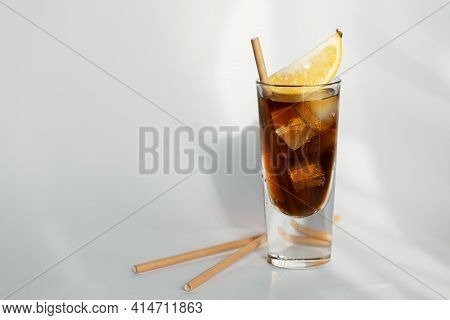 Glass Of Cola With Ice, Lemon And Straw On White Background